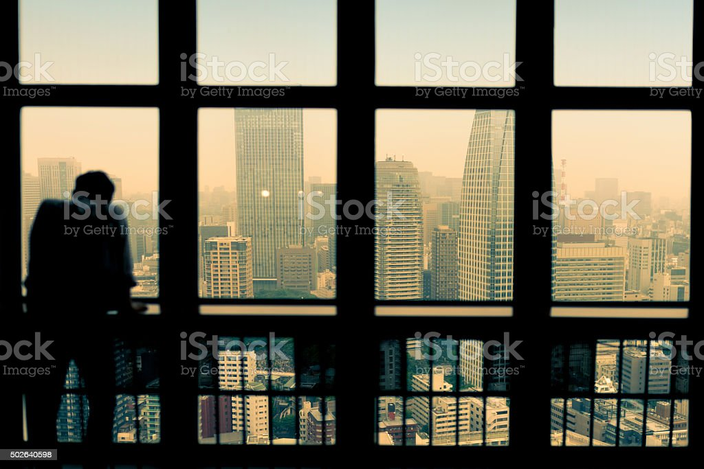 silhouette of a person looking at city stock photo
