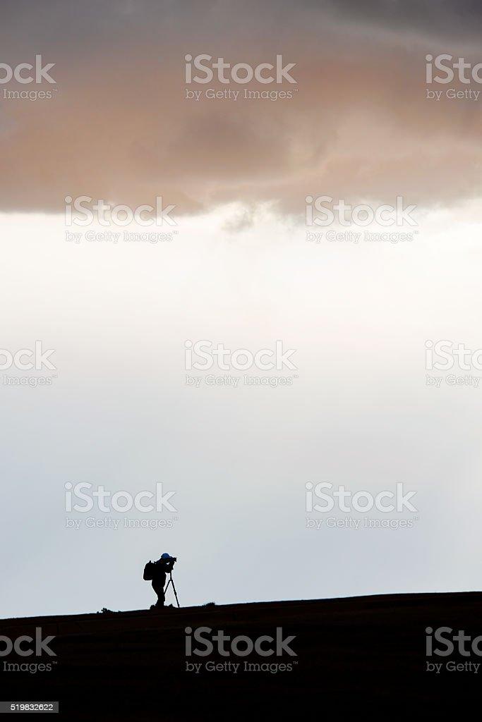 Silhouette of a Photographer on a Mountain Peak stock photo