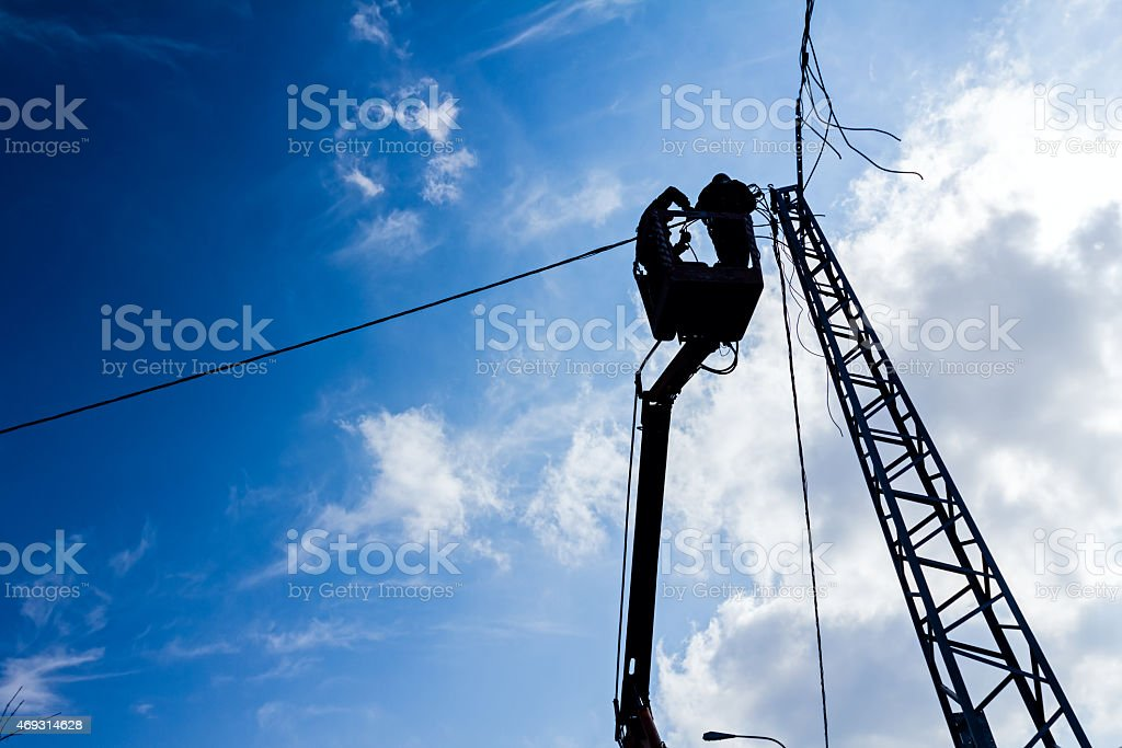 Silhouette of a power line team at work stock photo