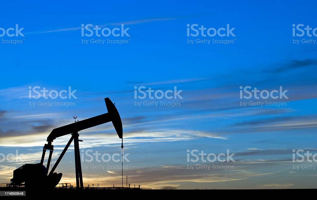 Silhouette of a pump jack against the blue night sky stock photo