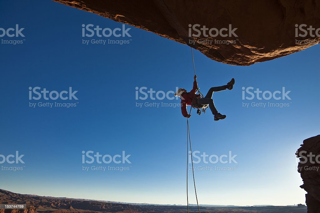 Silhouette of a rock climber rappelling down a cliff stock photo