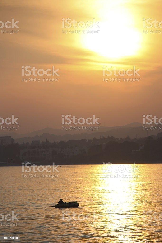 Silhueta de um Barco de Pesca de borracha definição flutuante através do reflexo do sol foto de stock royalty-free