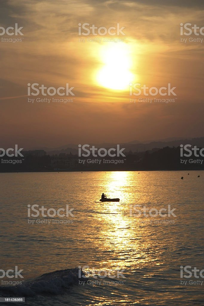 Silhouette of a rubber boat floating through setting sun's reflection royalty-free stock photo
