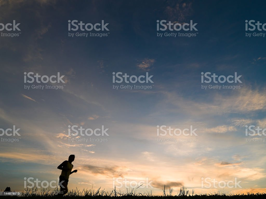 A silhouette of a runner at dusk royalty-free stock photo