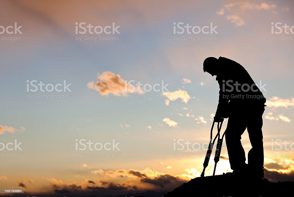 Silhouette of a Sad Injured Man With Crutches stock photo