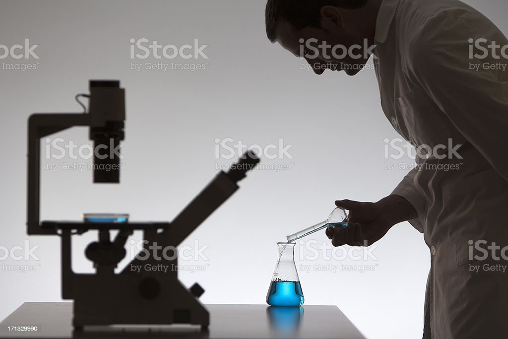 Silhouette of a scientist working on creating new medications royalty-free stock photo