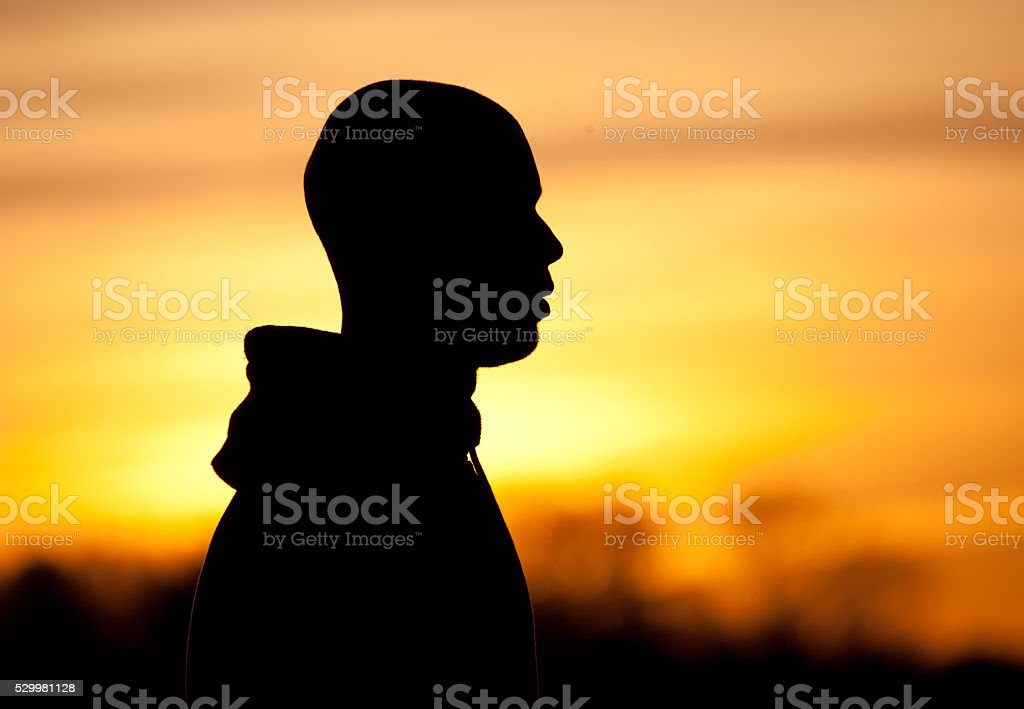 Silhouette of a shaved male at dawn stock photo
