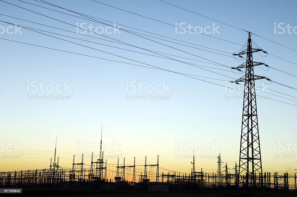 Silhouette of a single tower on a power station at sunset stock photo