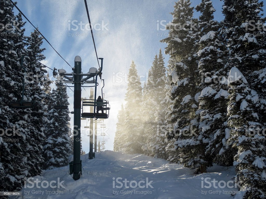 Silhouette of a skier and chair lift in blowing snow stock photo