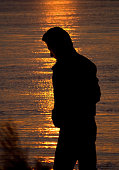 Silhouette of a solitary man by the sea at sunset