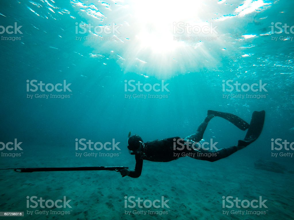 silhouette of a spear fisherman in the blue sea stock photo