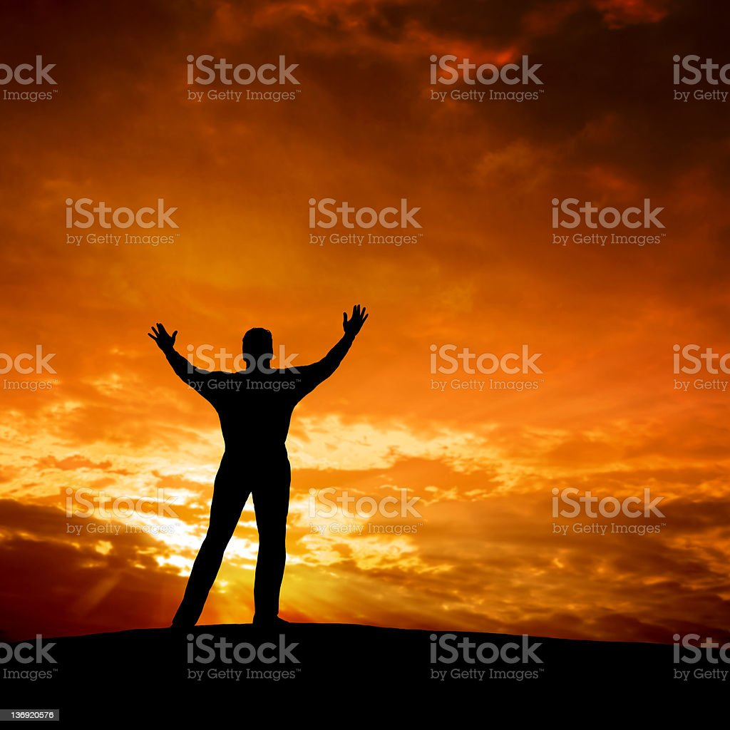 Silhouette of a spiritual man against orange sky royalty-free stock photo
