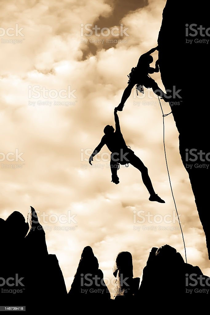 Silhouette of a team of climbers who appear to be in danger royalty-free stock photo
