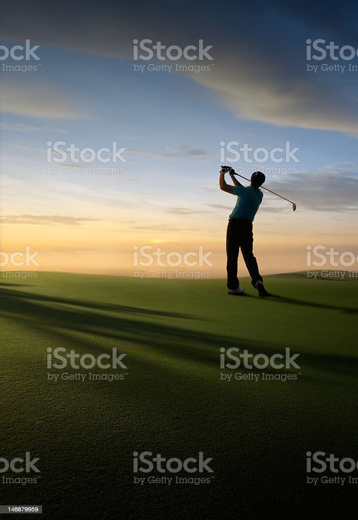 A silhouette of a tee off at a golf course at dawn stock photo