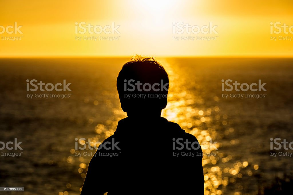 Silhouette of a teenager boy on sunset stock photo