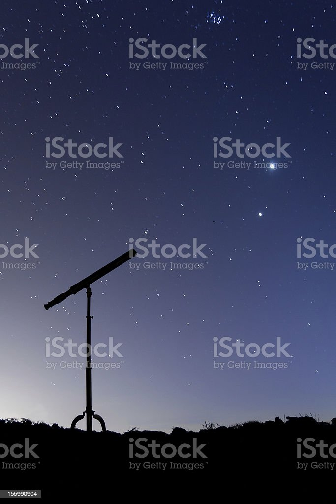 Silhouette of a telescope against starry night sky stock photo