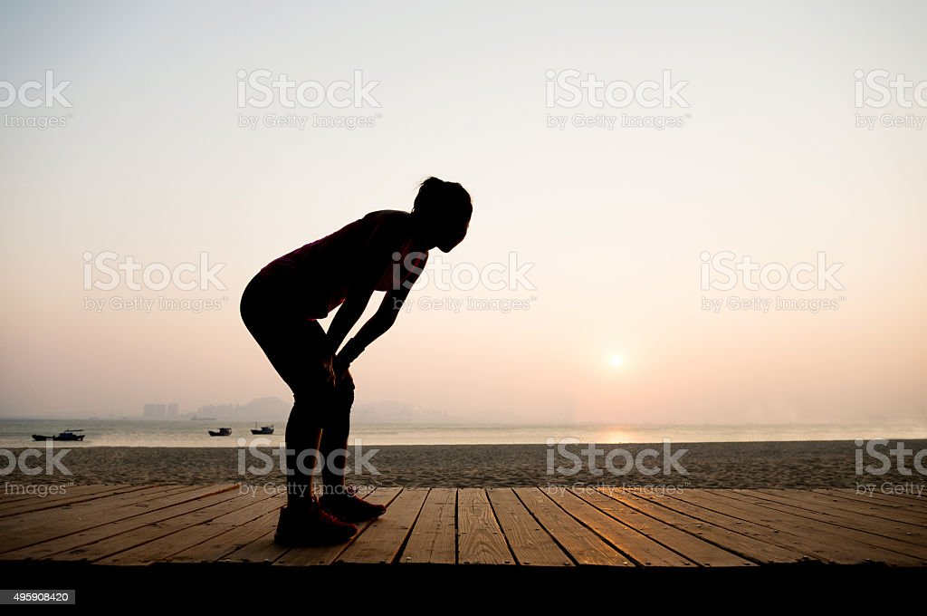 Silhouette of a tired runner stock photo