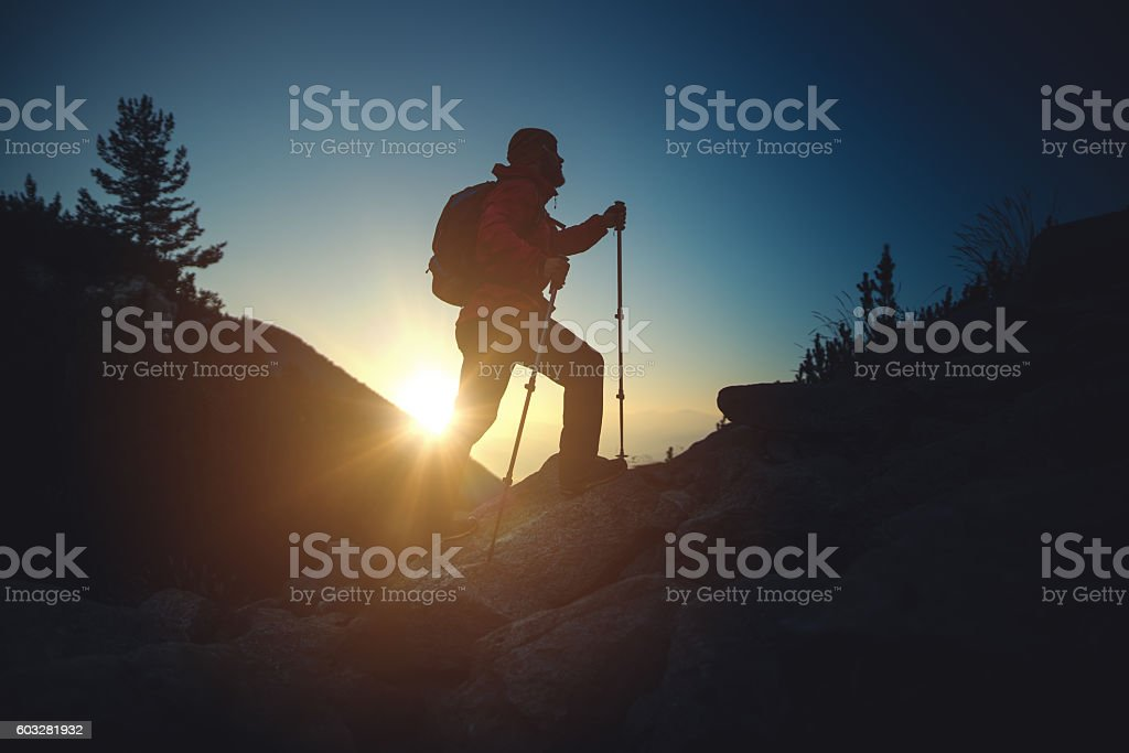 Silhouette of a traveler climbing on top of mountain stock photo