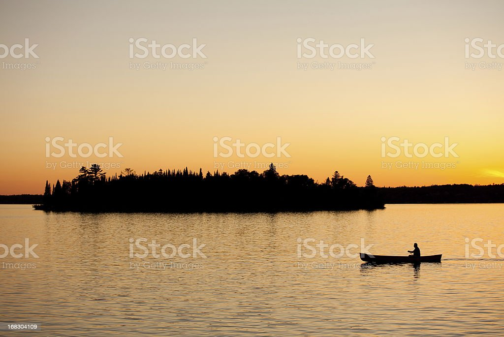 Silhouette of a Unrecognizable Male Canoeing in Ontario Canada stock photo