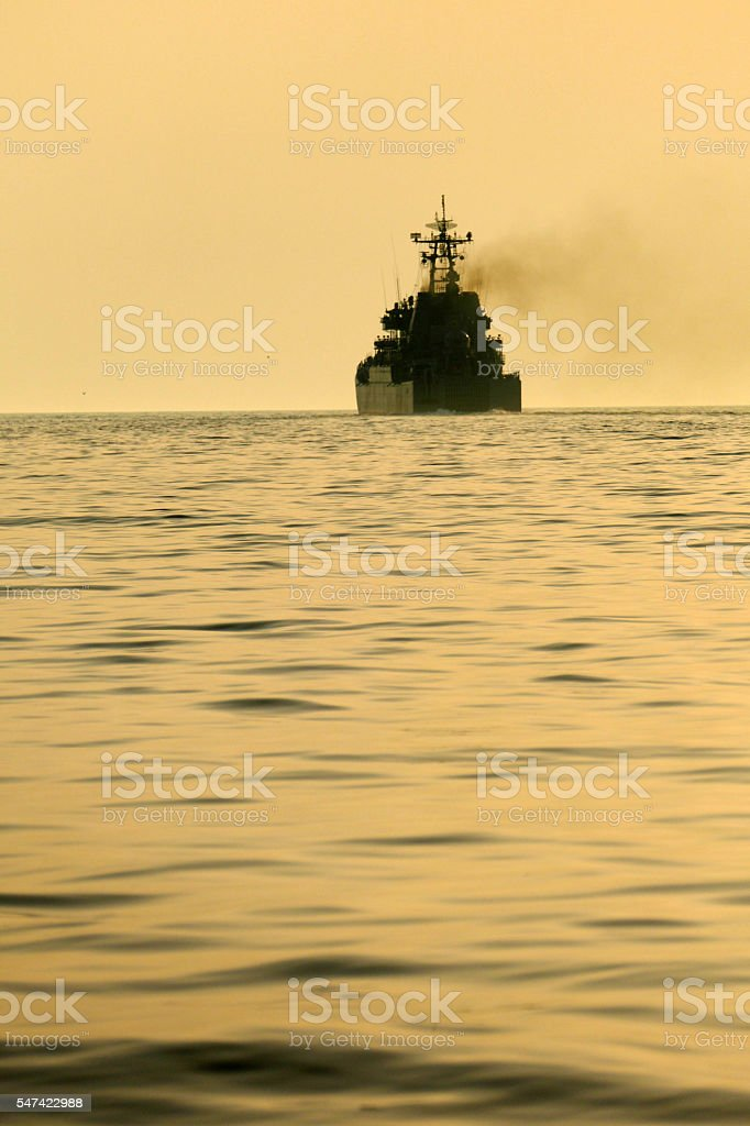 silhouette of a warship at sunset stock photo