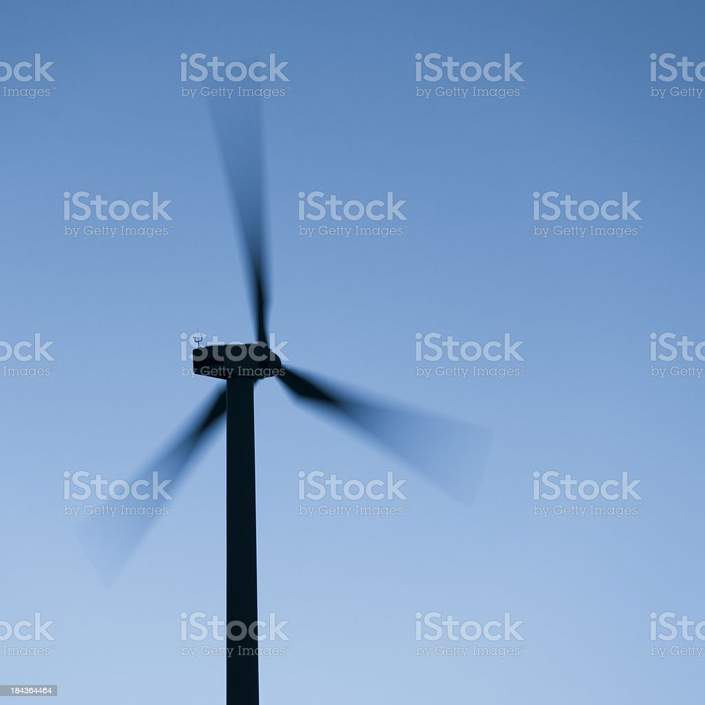 Silhouette of a wind turbine against blue sky at dusk royalty-free stock photo