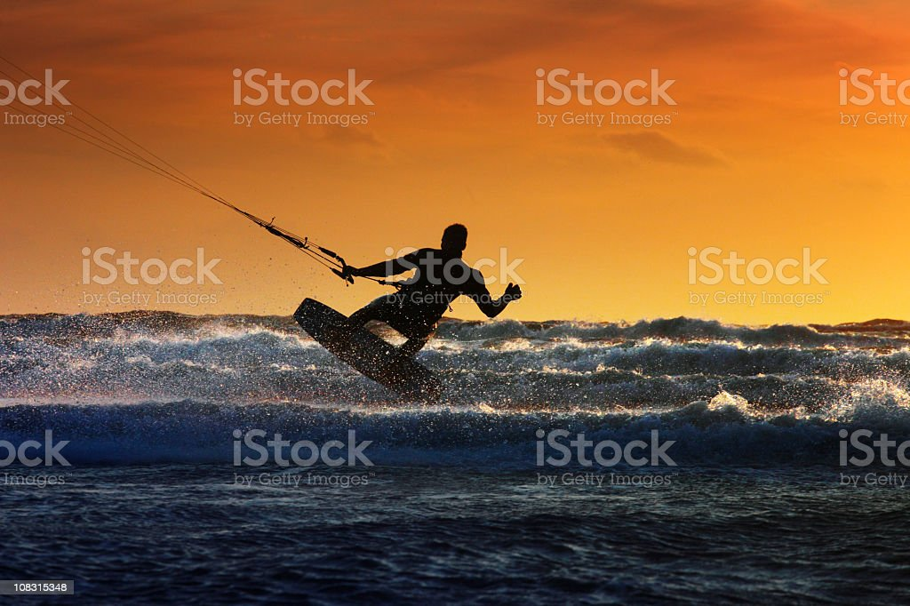 Silhouette of a windsurfer riding along the waves royalty-free stock photo