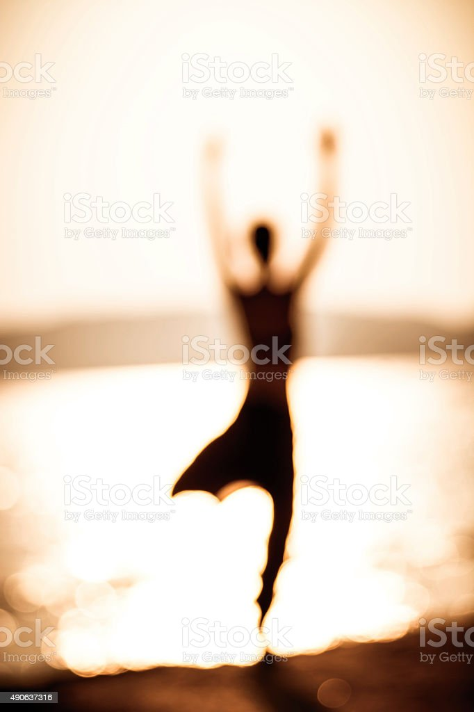 Silhouette of a woman at the beach stock photo