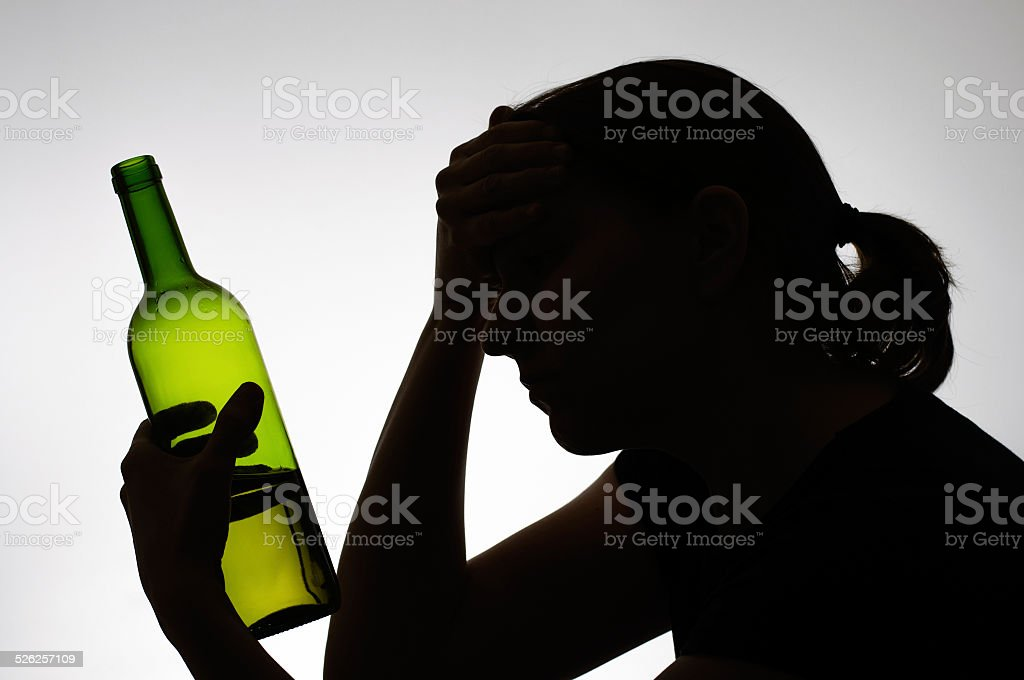 Silhouette of a woman holding a bottle stock photo