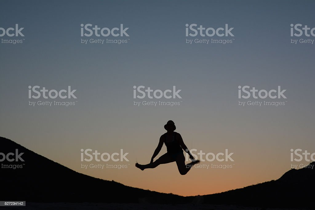 Silhouette of a Woman Jumping After Sunset royalty-free stock photo