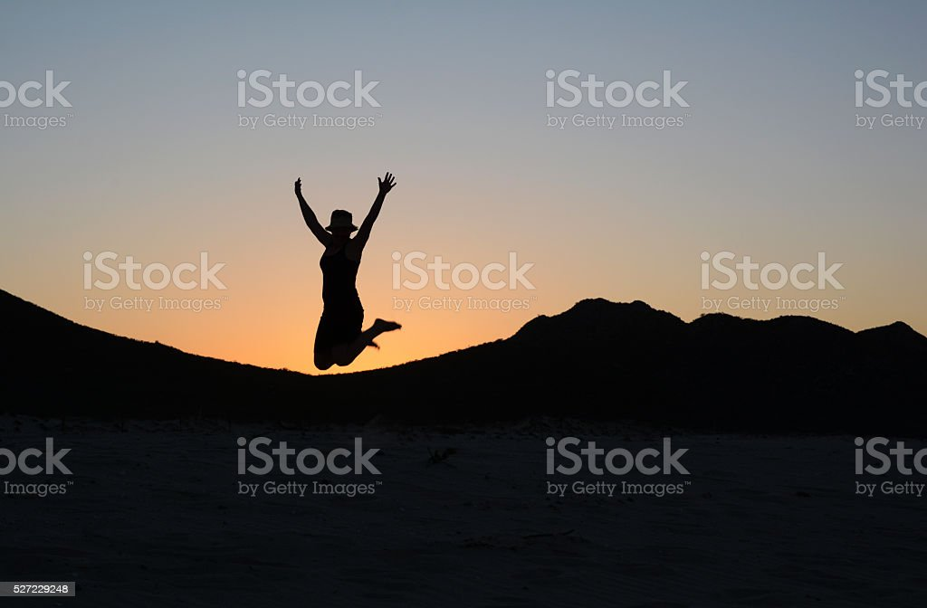 Silhouette of a Woman Jumping in the Air at Sunset royalty-free stock photo