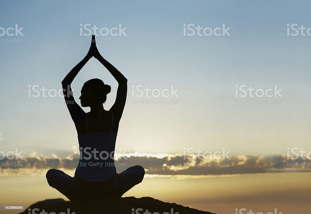 Silhouette of a woman meditating at sunrise royalty-free stock photo