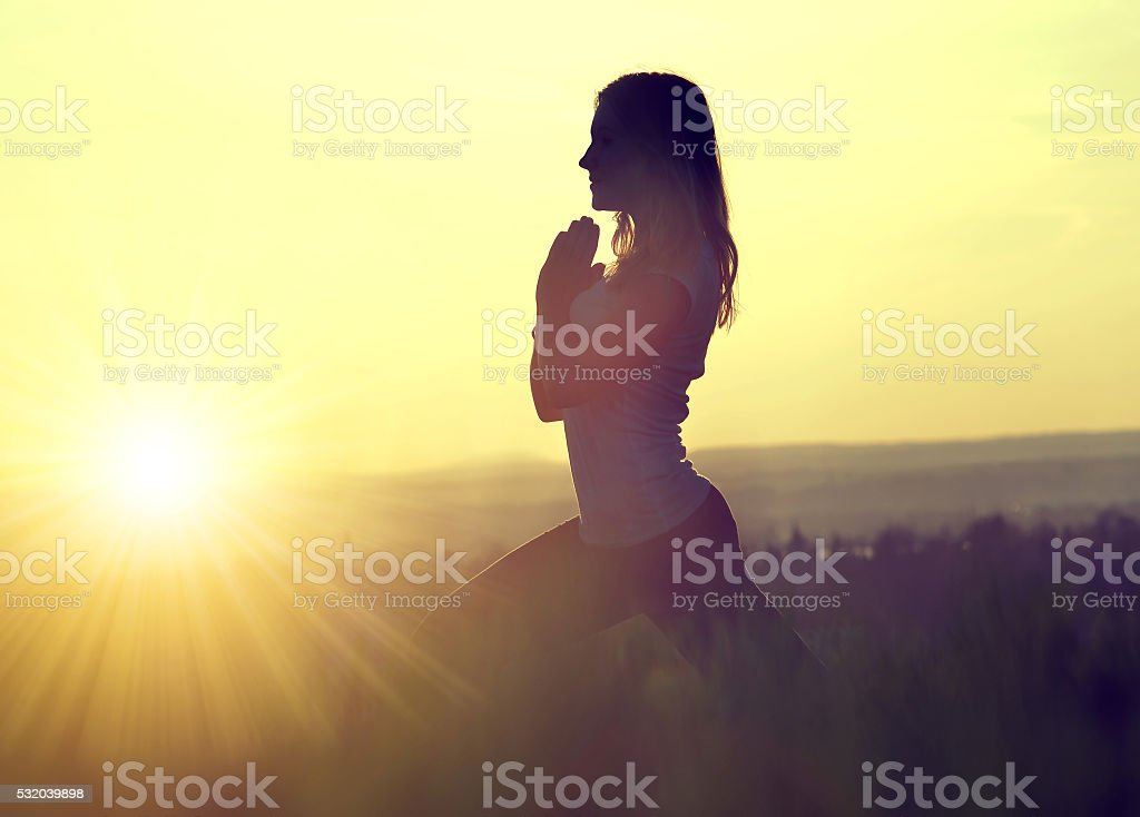 Silhouette of a woman meditating on a meadow stock photo