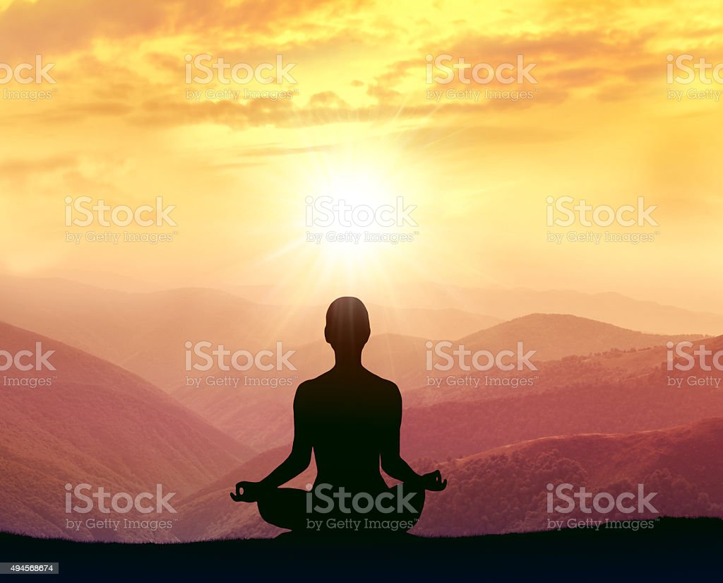 Silhouette of a woman practicing yoga in the mountains stock photo