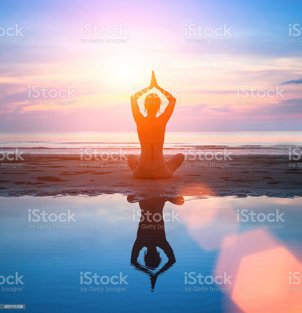 Silhouette of a woman practicing yoga on the beach stock photo