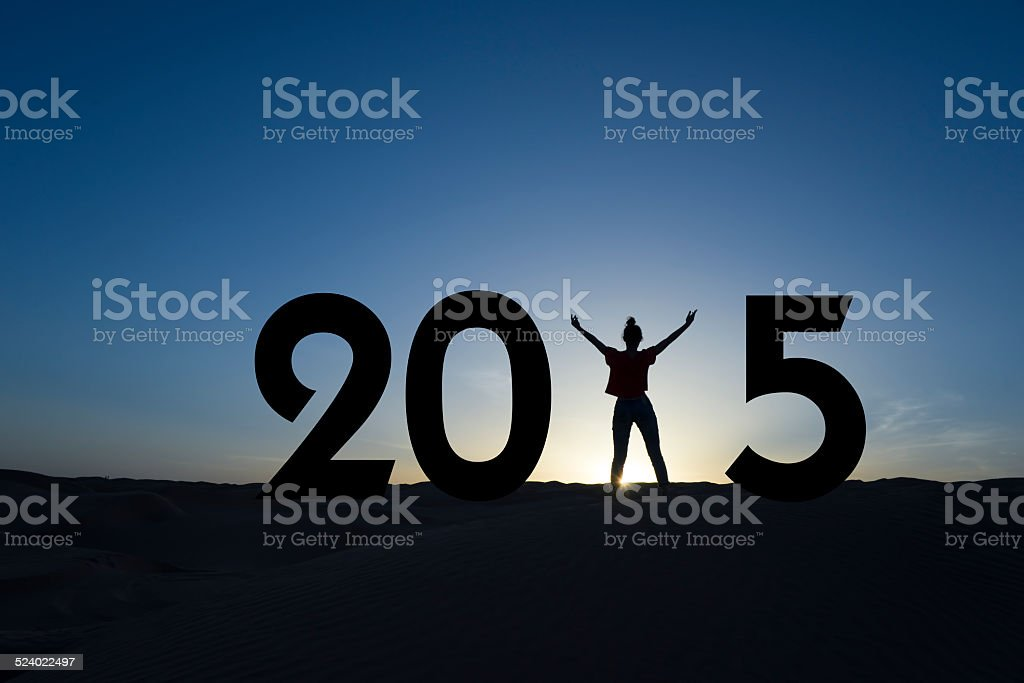 2015, silhouette of a woman standing in the sunrise stock photo