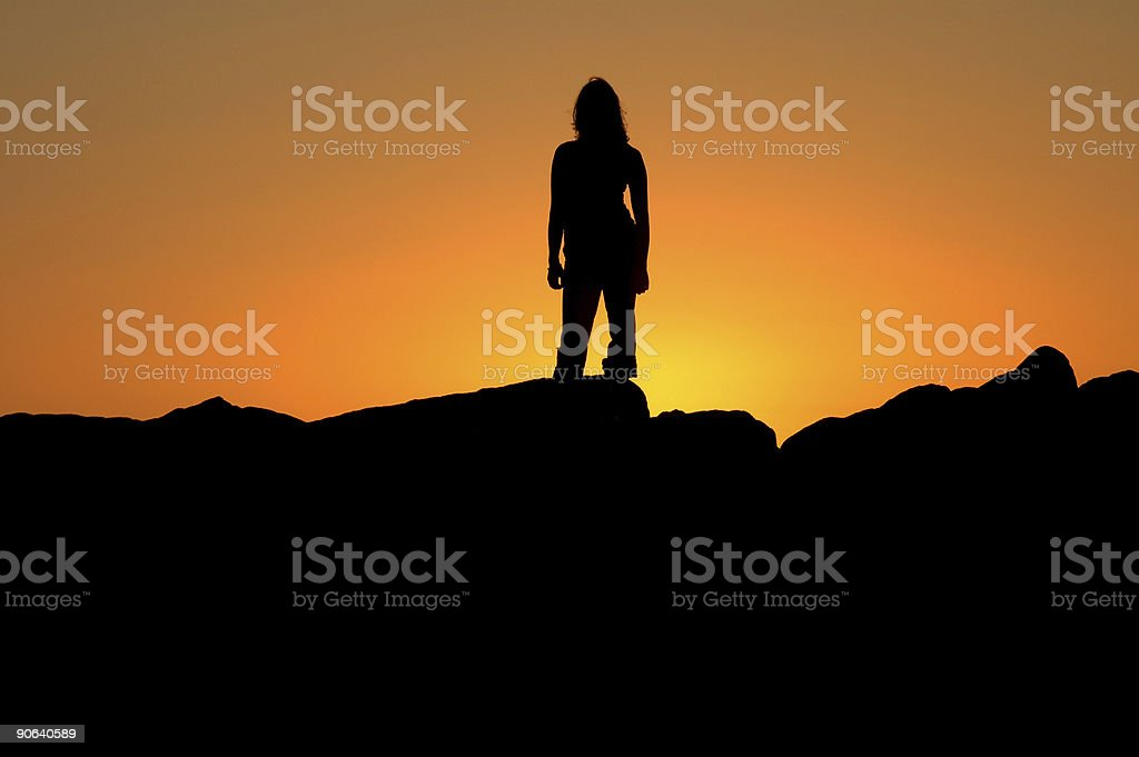 A silhouette of a woman that is standing on a mountain royalty-free stock photo