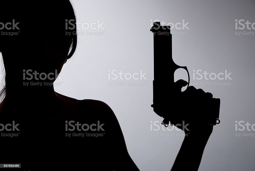Silhouette of a woman with gun stock photo