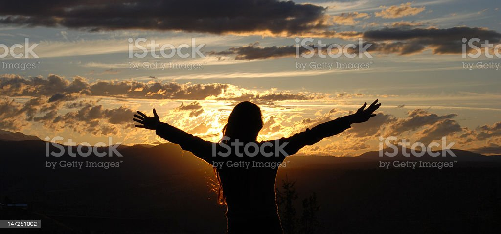 A silhouette of a woman with her arms open in the sunset royalty-free stock photo