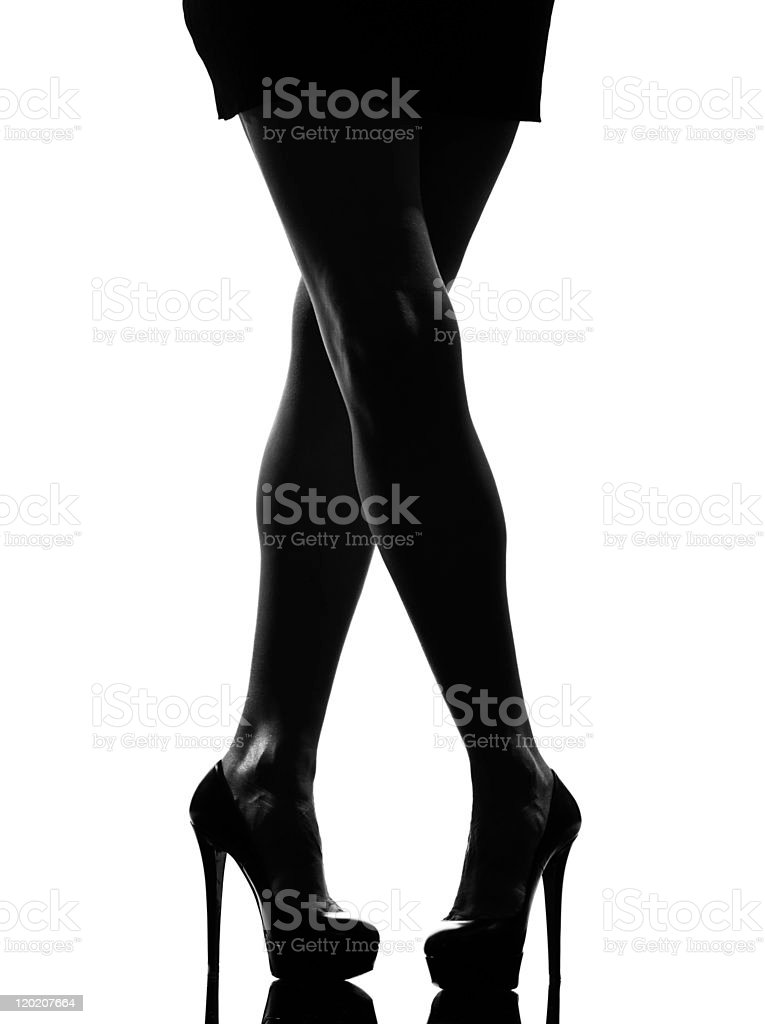 A silhouette of a woman's legs crossed wearing high heels stock photo