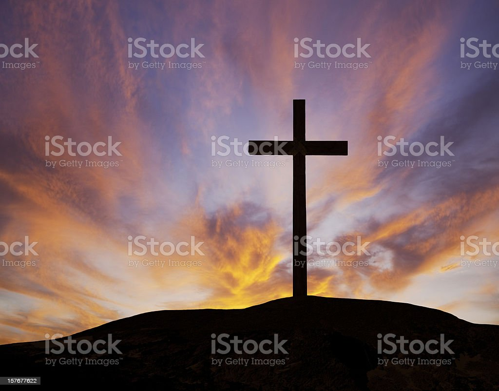 Silhouette of a wooden cross on a hill with a sunset stock photo