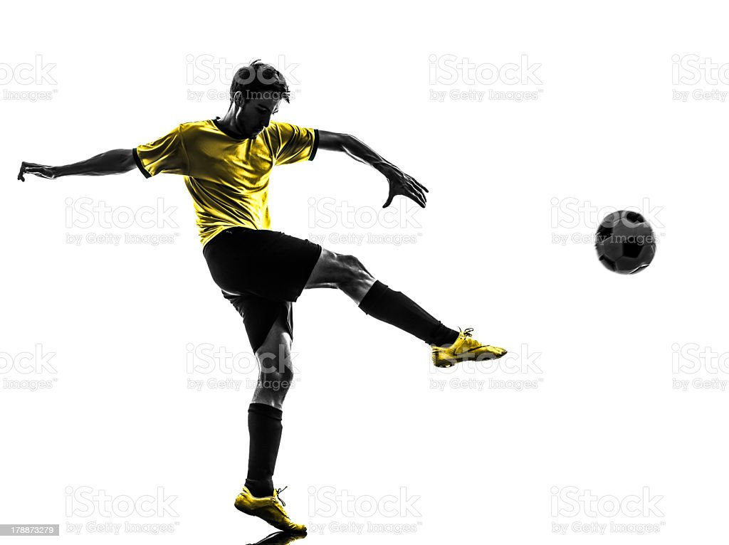 Silhouette of a Young Brazilian soccer player kicking a ball stock photo