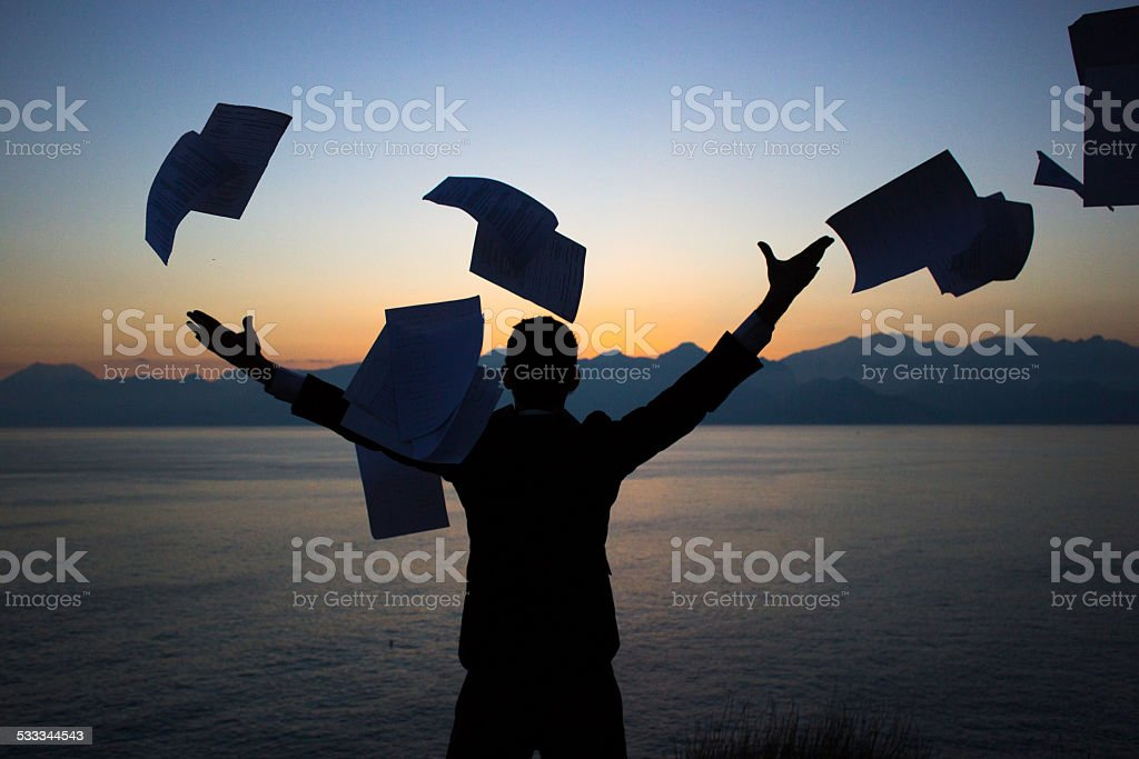Silhouette of a young businessman throwing away business documents stock photo