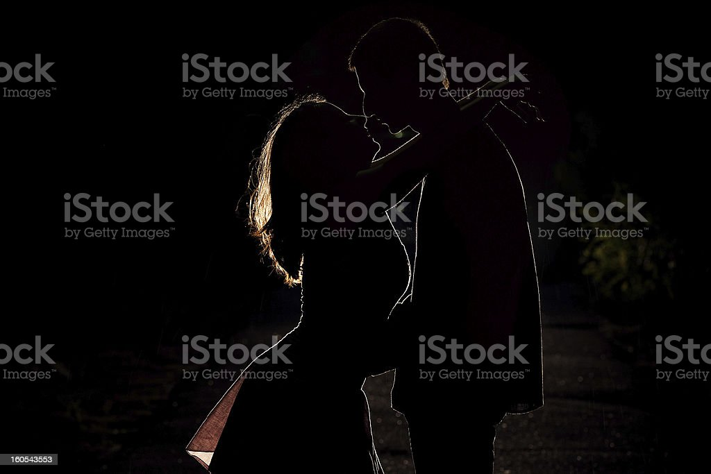 Silhouette of a young couple in the dark royalty-free stock photo