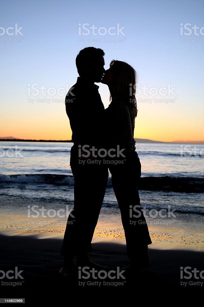 Silueta de pareja joven beso en la playa foto de stock libre de derechos