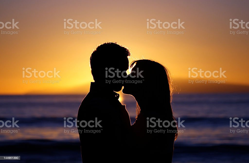 Silhouette of a young couple kissing on a sunset beach royalty-free stock photo