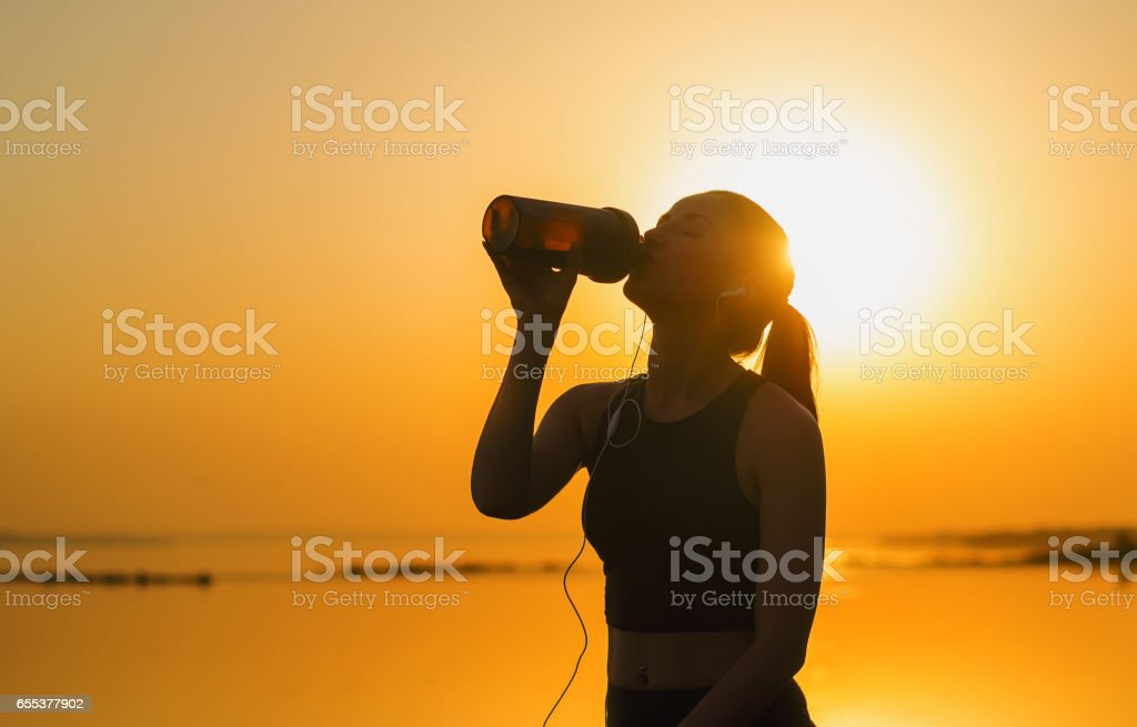 Silhouette of a young girl who drinks a protein cocktail stock photo