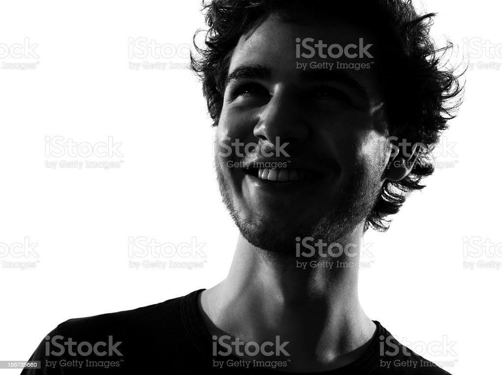 A silhouette of a young man showing joy and smiling stock photo