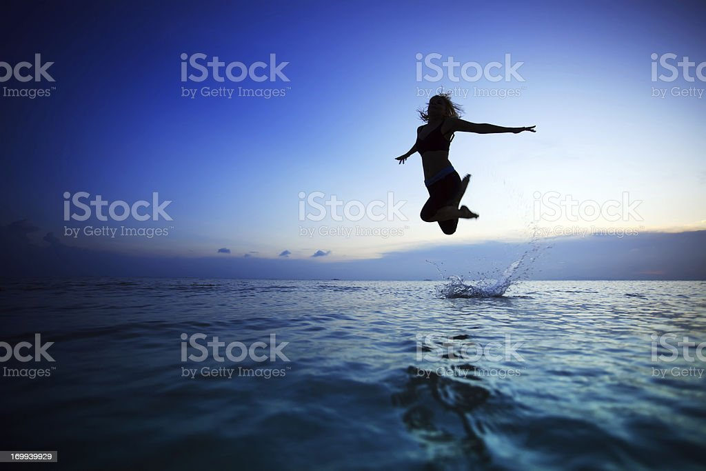 Silhouette of a young woman jumping in the water royalty-free stock photo