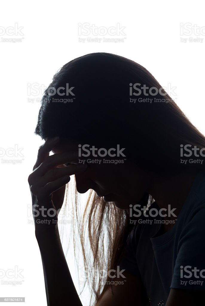 Silhouette of a young woman keep her head stock photo