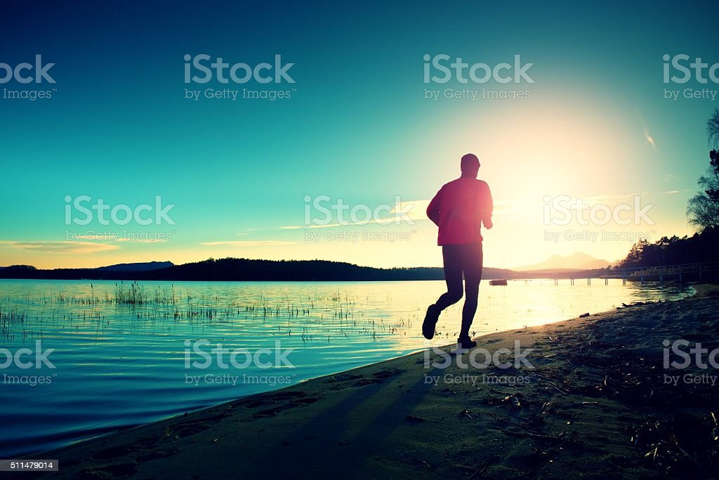Silhouette of active man exercising on the beach at sunset. stock photo